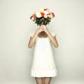 Brautjungfer hält sich Blumen vor den Kopf