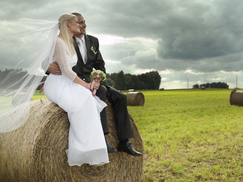 Braut und Bräutigam sitzen auf einem Heuballen