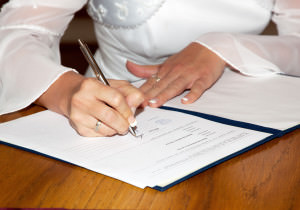 The bride signing the marriage certificate